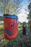 Red dog waste bin. Responsible pet ownership. Cleaning up dog mess. Bin outside UK park Royalty Free Stock Images