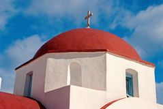 Red dome with cross detail in Mykonos, Greece. Church building architecture on sunny outdoor. Chapel on blue sky. Religion and cult concept. Summer vacation on royalty free stock images