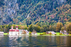 Red domes of the church. Picture taken from on board tourist boats. The concept of ecotourism. Magic Monastery of St. Bartholomew at Lake Königssee. Red domes royalty free stock photography