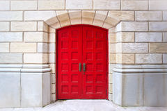 Red door. On white brick background royalty free stock photography