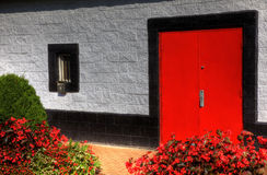 The Red Door. A large red door against painted bricks Stock Image