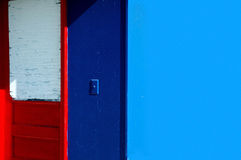 Red door. On blue wall Stock Photos