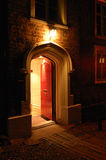 Red Door. Old fashioned wooden door open and inviting from a dark cobbled street Stock Photo