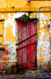 Red door. Weather red door on distressed yellow wall Royalty Free Stock Photography