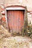 Red door. An unkept  basement door on an old abandoned building Royalty Free Stock Images