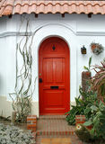 Red Door. A red arched door in a stucco house and plants Stock Photos