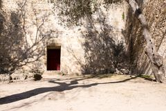 A red door as the entrance to a fortress in a desert environment stock photos