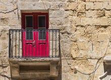Red door and a balcony, Valletta, island Malta. Old traditional building made of stone bricks with a balcony and a red door. Valletta, capital of island Malta Royalty Free Stock Photos
