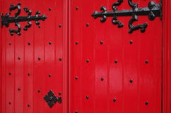 Red door with black iron trim. Close up of a red door with black iron trim Stock Image