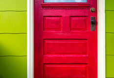 Red door. On a bright green house Royalty Free Stock Image