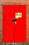 Red door double lock on brick wall. Stock Photography
