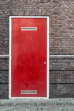 A red door embedded in a stone wall. A red door embedded in a historic brick stone wall outdoor Stock Photos