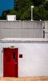 Red door and exit sign on small building in Towson, Maryland. Stock Photos