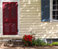 Red Door and Red Flowers, Pretty Home. Two weathered steps lead to the red door, and red flowers sit at the entrance. The red is good contrast to the light stock photos