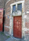 Red Door and Gable Stone for the Blacksmith`s Guild, Waag House, Amsterdam, The Netherlands. Pictured is a red door and gable stone for the Blacksmith`s Gild on royalty free stock photo