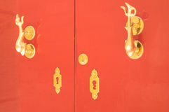 Red door with gold handle on antique building Stock Images