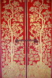 Red door with gold painting. At the Emerald Buddha temple, Bangkok, Thailand Stock Image