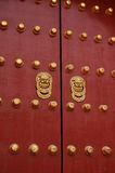 Red door with golden lion handle. A pair of golden lion handles of an ancient Asian door Stock Photography