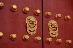 Red door with golden lion handle. A pair of golden lion handles of an ancient Asian door Royalty Free Stock Photos