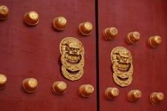 Red door with golden lion handle. A pair of golden lion handles of an ancient Asian door royalty free stock photos