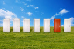 Red door among many white ones. Challenge unknown future concept Royalty Free Stock Photo