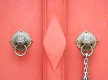 Red door and metal door latch with two lion head shapes. For background or wallpapers royalty free stock photography