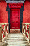 Red door at a monastery. Bridge and a door in a Buddhist monastery in Ladakh, Kashmir, India Stock Photography