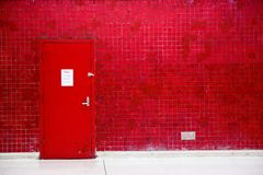 Red door and mosaic wall Royalty Free Stock Photo