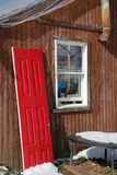The Red Door. Off it`s hinges. The Red Door is leaning against the wooden house Royalty Free Stock Photos