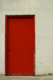 Red door in an off-white stucco wall Stock Photography