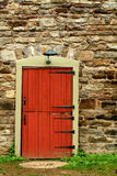 Red door on a old stone building Royalty Free Stock Photos