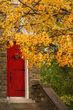 Red Door and Orange Autumn Leaves Royalty Free Stock Photography