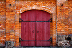 Red door in red brick wall. Old Red wooden door in red brick wall royalty free stock photos