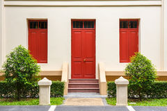 Red Door , red window on Cream Wall on red staircase with small Royalty Free Stock Images