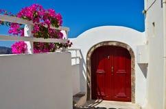 Red door in Greece. Red door and pink flowers in Oia, on the Greek island of Santorini Stock Images