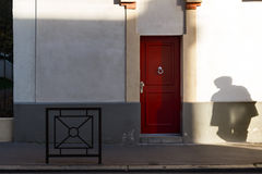The red door. Shadow shape comming to the door Royalty Free Stock Image