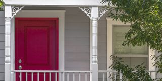 Red door and sliding window of a home with balcony. Home with bright red front door and sliding glass window. It also features horizontal wall siding and a royalty free stock photography