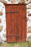 Red wooden door in stone boulder wall. Old red wooden door in stone boulder Wall of Swedish farm building Stock Image