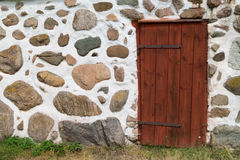 Stone boulder wall with red wooden door Stock Photography