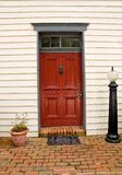 Red Door to a House. Main entrance to an old house through a red door Stock Photo