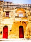 Red door typical street in Gozo, Malta. Lovely red door on the island of Gozo balcony stock image