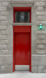 Red Door on an Urban Firehouse. A bight red door and window mark the pedestrian entrance to an urban firehouse stock photography