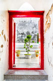 Red door through the wall. Looking through the entrance to a Thai temple Royalty Free Stock Photo