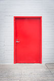 Red Door in White Brick Wall. Red painted metal door and frame set into white painted brick wall Stock Photography
