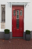 Red door on a white wall with a glass Royalty Free Stock Image