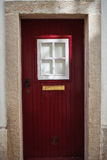 Red door with white window. With a gold mailbox royalty free stock photos