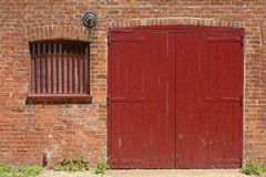 Red door and window in brick wall. Red painted wooden barn door and window with bars in old brick wall to quayside building at Dell Quay in Chichester Harbour Royalty Free Stock Photography