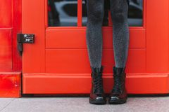 Black women`s boots. Red door and women`s legs in black boots royalty free stock photo