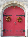 Red doors. Beautiful red church doors with marble framing and old fashion huge wrought iron hinges along with wreathes hanging to decorate and make everyone Royalty Free Stock Images