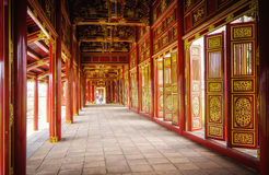 Red Doors, Imperial Citadel, Hue, Vietnam. Red doors, wall panels, and ceiling, painted with gold, provide a dramatic hallway in a building of the Imperial Royalty Free Stock Image